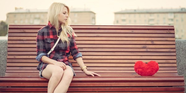 Sad lonely girl sitting on a bench near to a big red heart